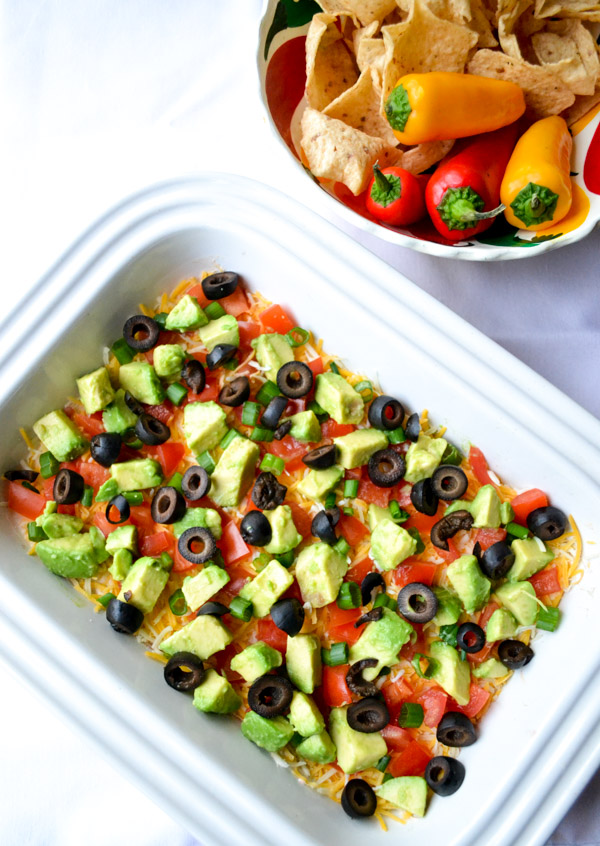 easy refried black beans in layered dip with chips and sweet peppers to dip