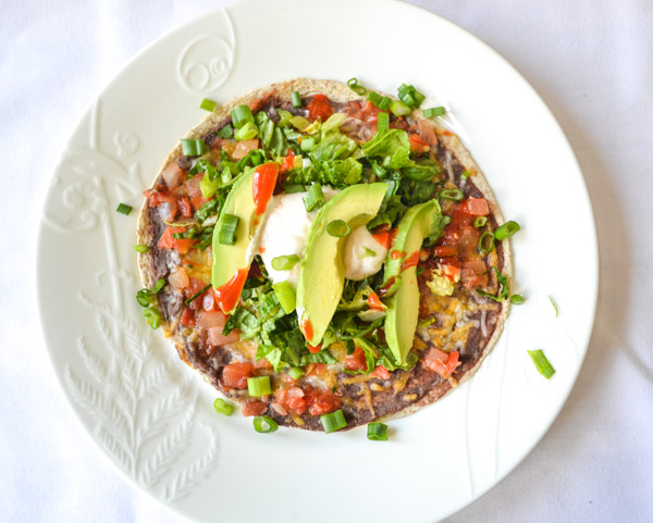 plated overhead view of refried black beans spread on tortilla with cheese, tomatoes, lettuce, Greek yogurt, green onions, avocado and hot sauce