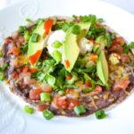 Close up of Refried Black Bean Tostada with Salsa, Green Onions, Greek Yogurt, Avocado and Hot Sauce
