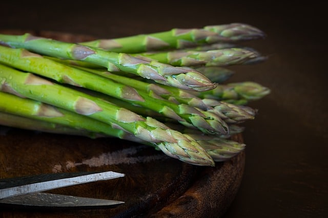 Asparagus Stalks on wooden surface with scissors