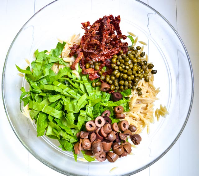 cooked orzo, julienned spinach, sundried tomatoes, capers and sliced Kalamata olives in bowl