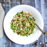 mediterranean orzo salad in white bowl with fork and line napkin