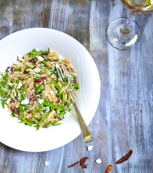 mediterranean orzo salad in bowl with fork and glass of white wine