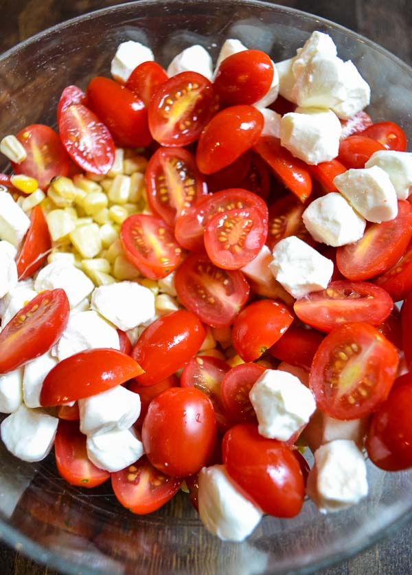 sliced grape tomatoes, grilled corn kernels and pearled mozzarella balls in bowl