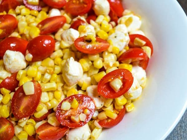 grilled corn and tomato salad in white serving dish