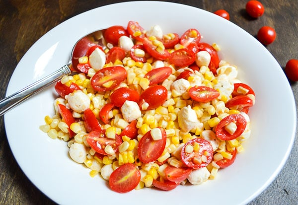 grilled corn and tomato salad tossed with white wine vinaigrette in serving bowl with serving spoon