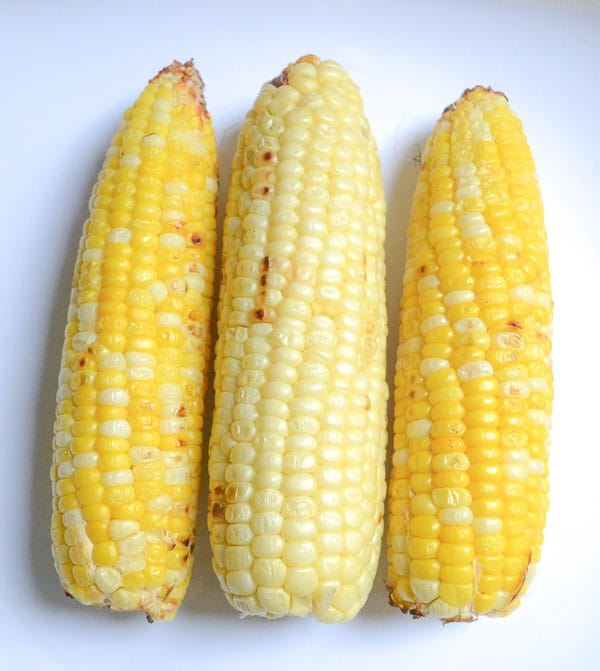 three ears of grilled corn on the cob on plate
