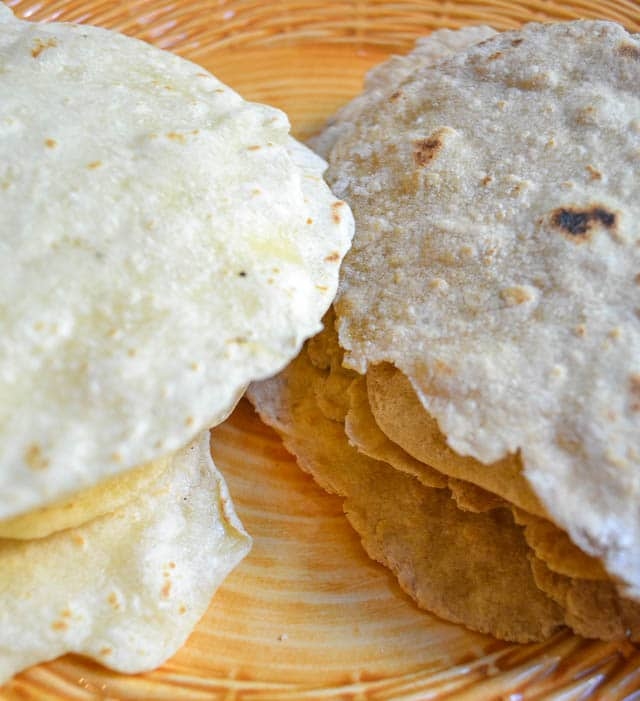 side by side close up of stacked homemade white and wheat tortillas on a plate