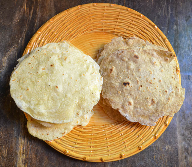 overhead view of healthy homemade white and wheat tortillas on yellow plate