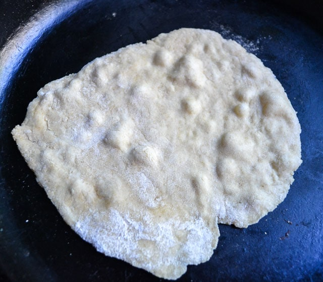 bubbling homemade wheat tortilla dough in cast iron skillet