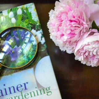 pink peonies in vase beside coffee table book with magnifying glass