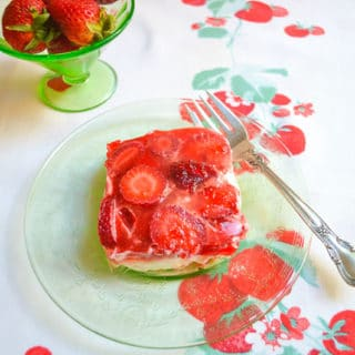 strawberry pretzel salad square on green glass plate with fork on a strawberry printed cloth