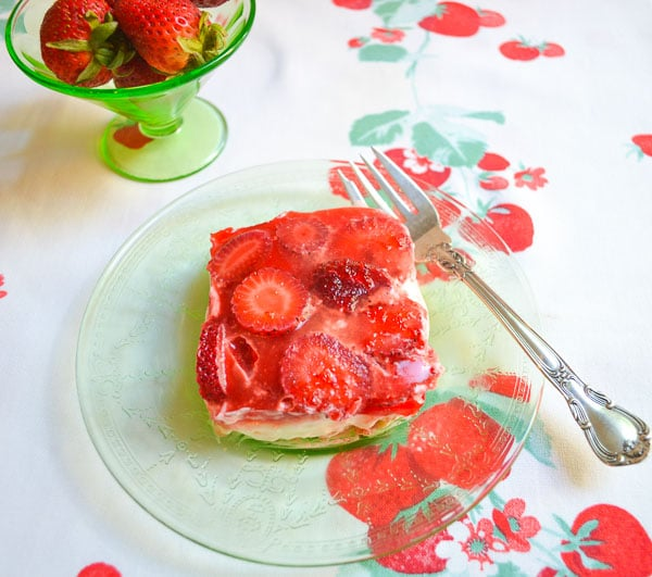 strawberry pretzel salad sliced square on green glass plate with fork on a strawberry printed cloth