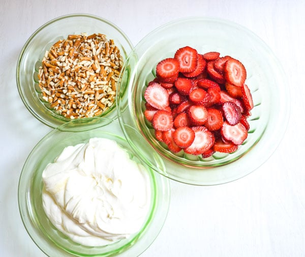 sliced strawberries, chopped pretzels and whipped topping in green glass bowls