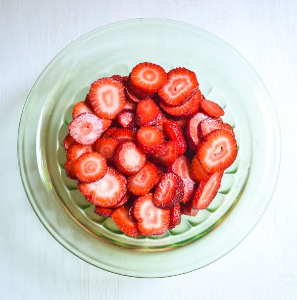 overhead view of sliced strawberries in green glass bowl