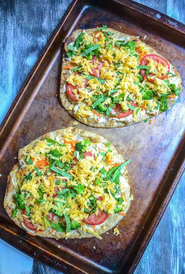 prepared rainbow vegetable hummus flatbreads with grated Cheddar cheese on cookie sheet