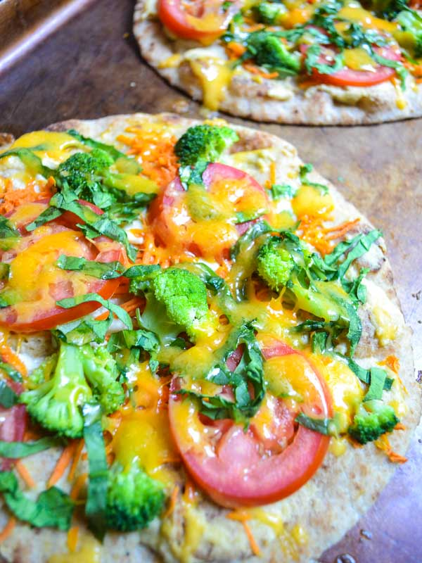 baked rainbow vegetable hummus flatbreads on cookie sheet