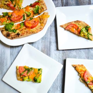 plated individual slices of rainbow vegetable hummus flatbreads and larger flatbread on serving plate