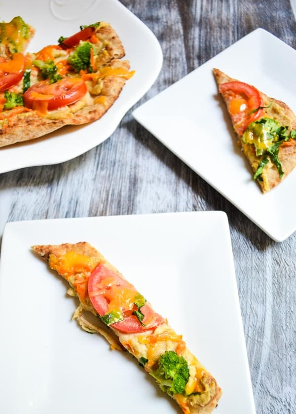 plated slices of rainbow vegetable hummus flatbread with larger flatbread on serving plate