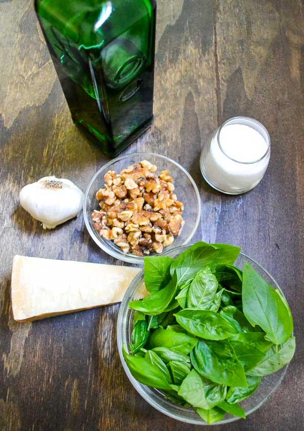 fresh basil, Parmesan, walnuts, whole garlic, salt and olive oil bottle mise en place