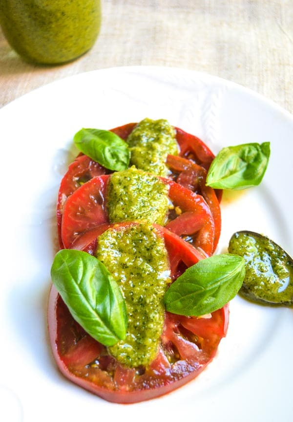 sliced Cherokee purple tomatoes drizzled with easy basil pesto and fresh basil