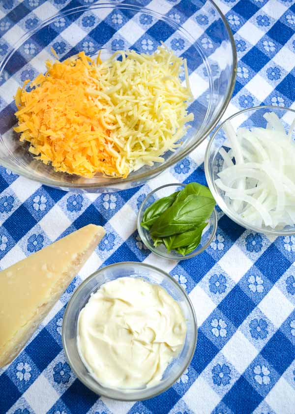 bowl of grated cheddar and mozzarella cheese, Parmigiano-Reggiano wedge, bowl of sliced onions, bowl of fresh basil leaves and bowl of mayonnaise on blue gingham cloth