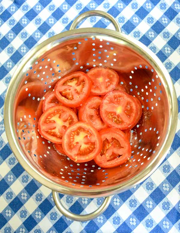 sliced tomatoes in stainless steel colander on blue gingham cloth