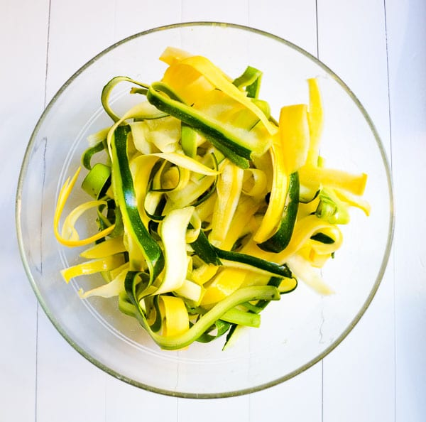 yellow squash and zucchini ribbons in glass bowl