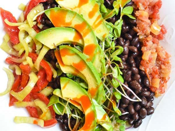 vertically layered Tangy Southwest Quiona Bowl with Lime Vinaigrette ingredients drizzled with hot sauce in bowl