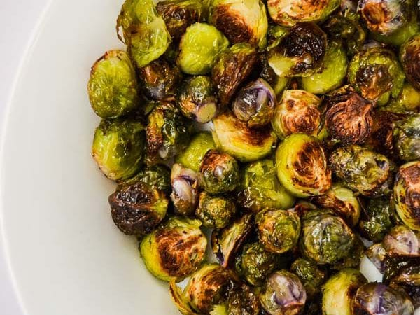 overhead of oven roasted brussel sprouts in white serving dish