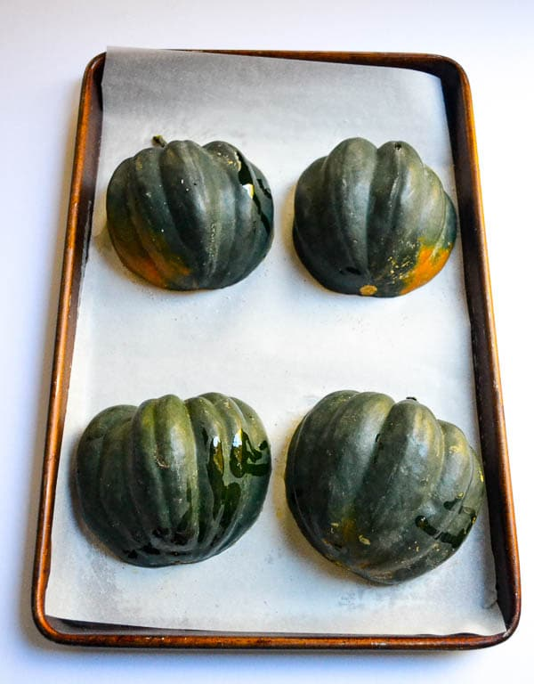 Four Acorn Squash Halves skin side down on parchment lined baking sheet