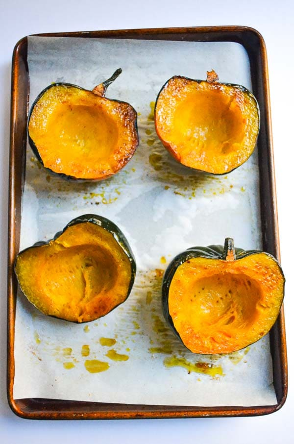 Four Cooked Acorn Squash Halves on parchment lined baking sheet