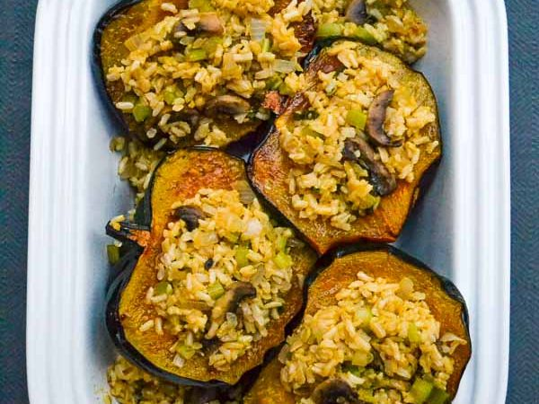 Four Vegetarian Stuffed Acorn Squash halves in casserole dish