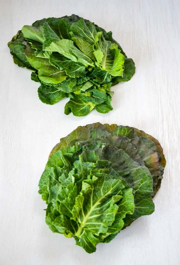 two stacks of cleaned raw collard leaves