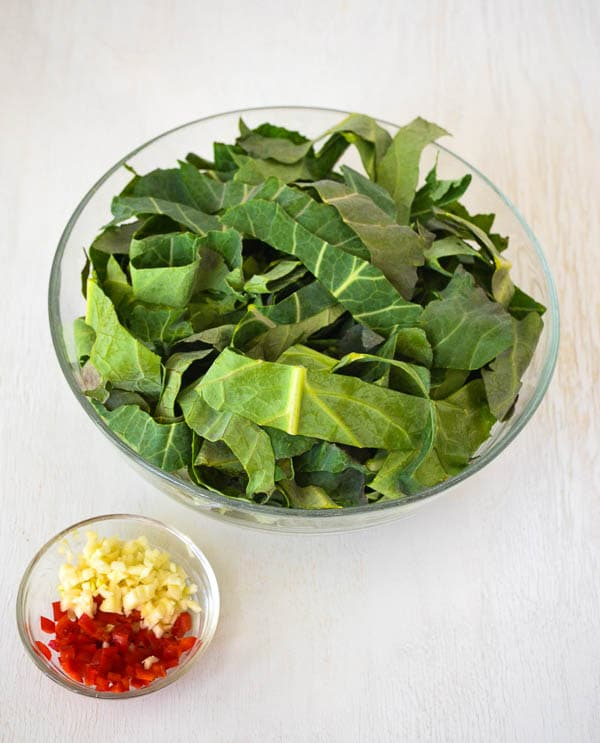 bowl of raw collard leaf ribbons and bowl of minced garlic with chopped red chili pepper