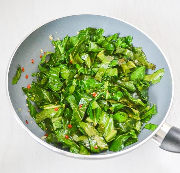 collard leaves tossed with garlic, pepper and oil mixture in sauté pan