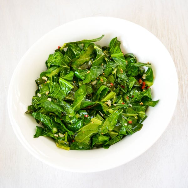 serving bowl of sautéed collard greens with garlic and pepper