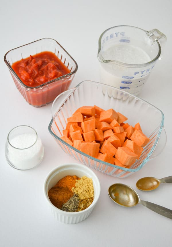 chopped sweet potato, crushed tomatoes, lite coconut milk, kosher salt and bowl of measured spices with measuring spoons