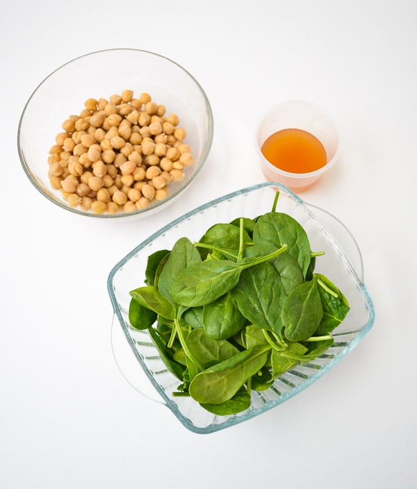 bowl of chickpeas, fresh spinach and measured vegetable broth