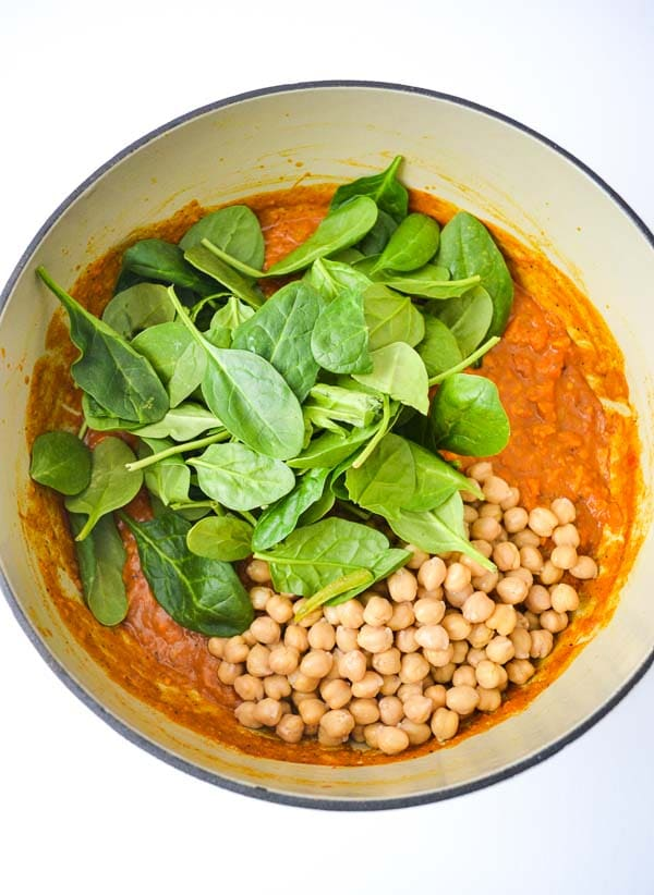 fresh spinach and chickpeas added to simmering sweet potato chickpea cury recipe