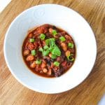 Bowl of Smoky Vegan Crockpot Chili garnished with cilantro sprigs and chopped green onion