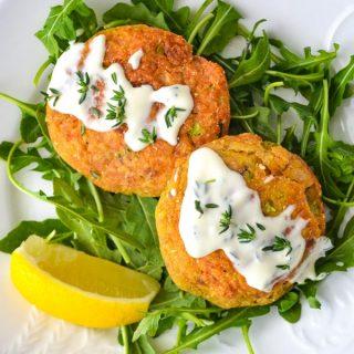 Easy Salmon Cakes with Lemon Thyme Aioli on bed of arugula with sliced lemon wedge