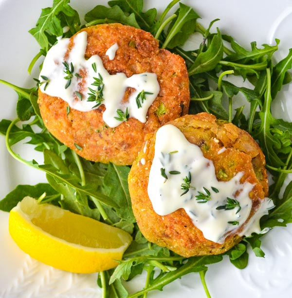 Easy Salmon Cakes with Lemon Thyme Aioli on bed of arugula with sliced lemon wedge