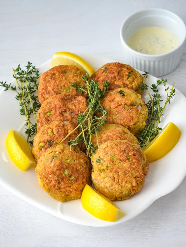 Prepared Easy Salmon Cakes on platter with lemon wedges and fresh thyme garnish