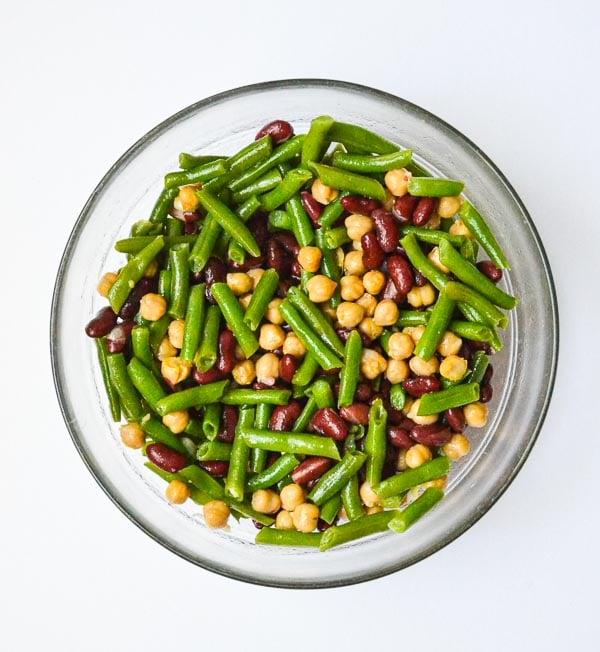 easy three bean salad tossed in mixing bowl with vinaigrette