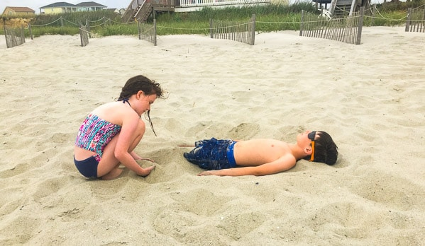 sister burying brother in sand at beach