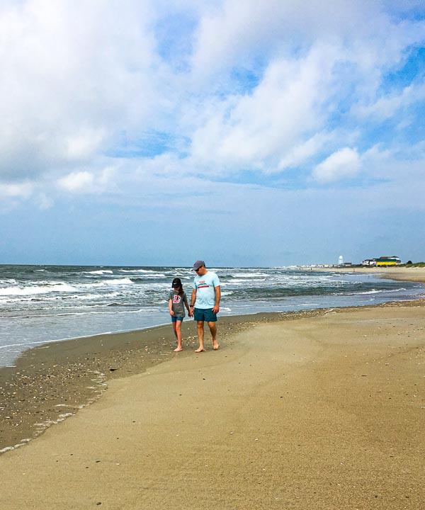 father and daughter holding hands while walking down beach