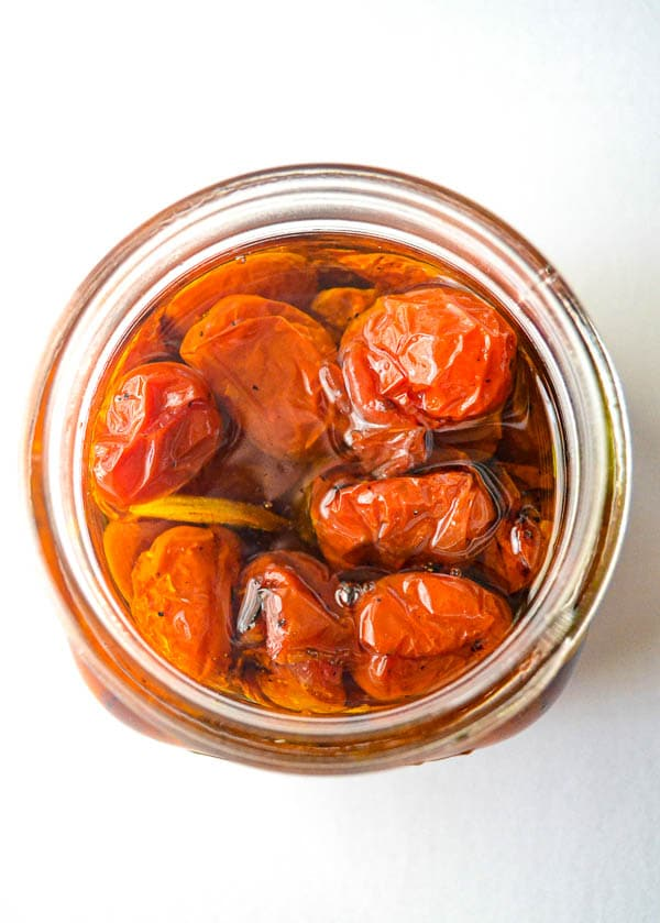 overhead of preserved roasted grape tomatoes in jar
