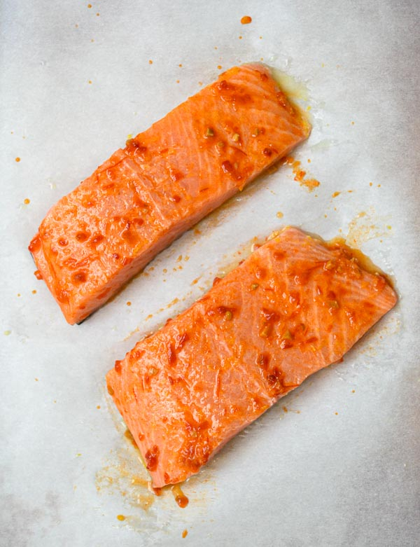 2 salmon fillets prepped on parchment-lined baking sheet