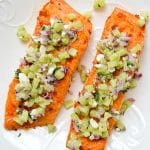 two servings of plated parchment baked harissa salmon with cucumber relish